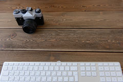 A camera and keyboard on a dark desk background Royalty Free Stock Image