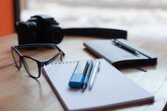 Camera, koffie, agenda en pennen op een houten lijst royalty-vrije stock foto