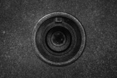 The camera lens is on the background texture of rough asphalt. Royalty Free Stock Photos