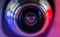 Camera lens and multi-colored backlight blue and red royalty free stock photos