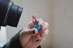 Camera lens and figurine Royalty Free Stock Image