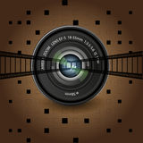 The camera lens and film on a brown background Royalty Free Stock Photography