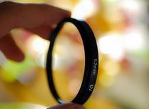 Camera lens filter being held. 52mm UV camera lens filter being held against bokeh background Royalty Free Stock Image