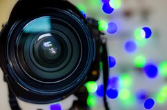 Camera Lens lights. Professional Camera Lens with bokeh Christmas lights background Stock Photos