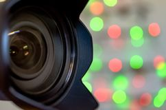 Camera Lens lights. Professional Camera Lens with bokeh Christmas lights background Stock Photography