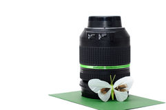 Camera lens for photographing nature. With a butterfly leaning against it, standing on a green underground Stock Images