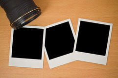 Camera lens with polaroid frames. Camera lens with blank polaroid frames on wooden background Royalty Free Stock Photography
