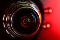 Camera lens and red backlight . Horizontal photography royalty free stock images