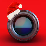 Camera lens with Santa hat. On a red background Royalty Free Stock Images