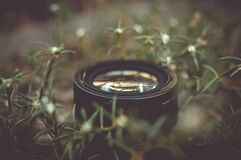 Camera Lens Surrounded by Green Outdoor Grass Royalty Free Stock Photography