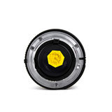 Camera lens with yellow flower behind lens aperture. Royalty Free Stock Photography