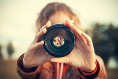 Through camera lens. Young woman looking through camera lens Stock Photos