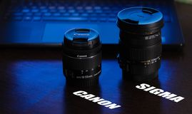 Camera Lenses Canon and sigma on the table with blue violet light from the background, laptop keyboard and touch pad and name writ royalty free stock image