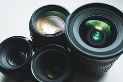 Camera lenses on a white surface. Close-up view of a group of camera lenses on a white surface Royalty Free Stock Photo