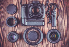Camera and lenses on wooden desk background. Stock Photo