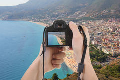 Camera in male hands taking picture of beautiful landscape Stock Photos