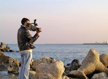 Camera man. A camera man waiting by the sea stock image