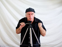 Camera man. Crazed looking man resting head on tripod and holding shutter release in hand looking intently at viewer while other hand holds tilt arm of tripod Royalty Free Stock Images