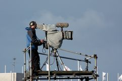 A camera-man in action. With a tv camera stock photography