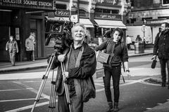 Camera man. London street a television production team arrive to film outside Lecester Square. There is a camera and sound man and girl PA. Monochrome stock image