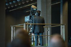 Camera man is making a video for the local news. The mourning ceremony for the victims of the collapsed bridge Morandi in Genova, Italy. A camera man in a suit royalty free stock photos