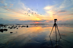 Camera met driepoot over zon het toenemen royalty-vrije stock foto's