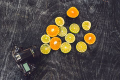 Camera and mixed fruits: ranges, lemons on wooden board Stock Photography
