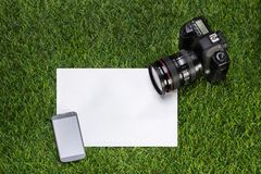 Camera with mobile phone and sheet of paper on the grass Royalty Free Stock Photography