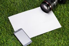 Camera with mobile phone and sheet of paper Royalty Free Stock Photo
