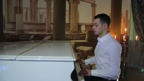 Camera motion, young cute brunette man in white shirt plays white grand piano stock footage