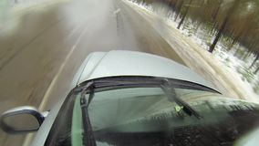 Camera mounted on a car when moving on winter road in forest. It goes sleet. 1080p stock footage