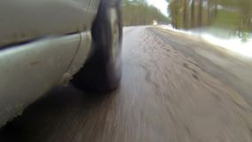 Camera mounted on a car when moving on winter road in forest. It goes sleet. Water splashes get on camera. 1080p stock footage
