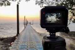 Free Camera Mounted On A Tripod Photograph The Pier And Sunrise, Focus On Screen Royalty Free Stock Photography - 152329117