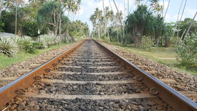 Camera move forward along the railway with exotic tropical nature at background. The rail tracks close up. Point of view. Of train moving along tracks in asia stock video footage