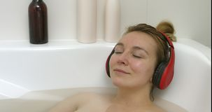 Relax in bath with music. The camera move on from left side to right, on woman in bath. Young woman is listening music while having relax in stock video footage