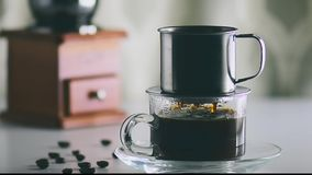 Camera movement antique coffee filter the filtered black coffee is poured into a clear glass. With coffee beans and Coffee grinder on white table stock footage