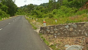 Camera Moves along Asphalt Road past Hills Tropical Plants. Camera moves along asphalt road past hills with green tropical plants stock video footage