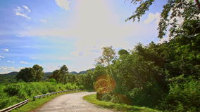 Camera Moves along Curvy Country Road among Hilly Landscape stock footage