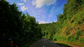 Camera Moves along Curvy Country Road among Hilly Landscape stock video footage