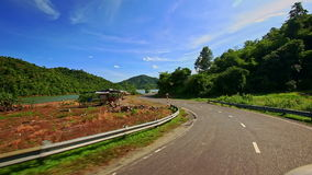 Camera Moves along Curvy Road past River among Landscape stock video footage