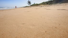 Camera Moves along Footprints Left on Wet Sand. Closeup camera moves along footprints left on clean wet sand beach to distant woman stock video footage