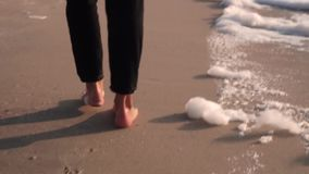 The camera moves along the footprints in the sand on the beach, stumbles upon women`s feet stock footage