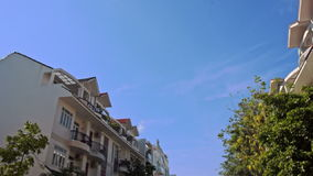 Camera Moves along House Tree Tops against Blue Sky stock video footage