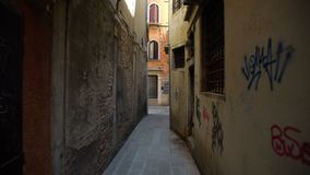 Camera moves along narrow street with old Venice houses