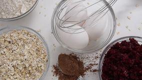 Camera moves along of red beet roots, oats and fresh eggs for healthy dessert cooking stock video