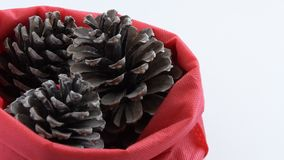 Camera moves along of three pine cones in red bag. Seasonal holiday background concept stock footage