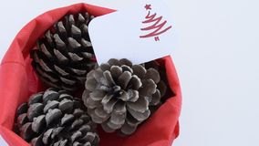 Camera moves along of three pine cones in red bag with seasonal greeting card. Seasonal holiday background concept stock footage