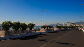 Camera moves along wide two-ways road among traffic. Past sea embankment against azure sky in Vietnamese resort city stock footage
