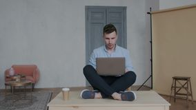 Camera moves around creative businessman while he sitting in the lotus position on the table with laptop and working stock footage