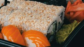 Camera moves away from stylish fresh sushi set with various kinds of sushi rolls, close up. View stock video